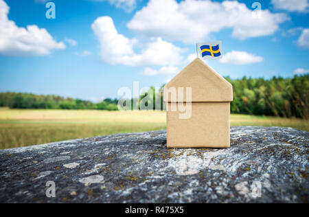 Cardboard house with a Swedish flag on a mossy rock. Scandinavian summer landscape. - Stock Photo