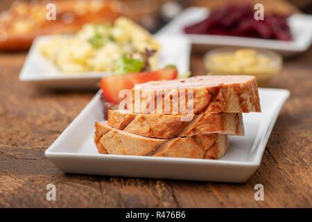 closeup of a bavarian leberkaese on dark wood - Stock Photo