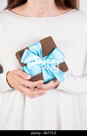 woman taking brown and blue gift - Stock Photo