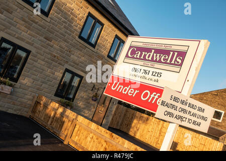 For Sale sign outside a brand new house - Stock Photo