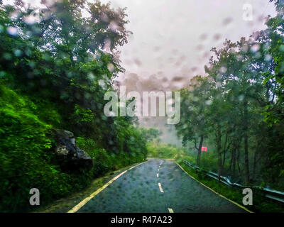 Driving down the mountain road in the rain, rain drops on the windscreen - Stock Photo