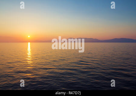 Magnificent sea sunset with calm water and foggy hills on the horizon. - Stock Photo