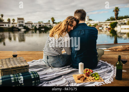 Rear view of a couple in love sitting side by side beside a lake. Couple on a day out sitting together with picnic food and drinks facing the lake wit - Stock Photo