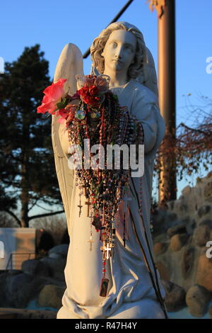 Angels holding armfuls of rosaries left as mementos of private requests at Our Lady of Guadalupe Shrine, frequented by Hispanics and immigrants, located in Des Plaines, Illinois. - Stock Photo