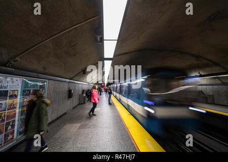 MONTREAL, CANADA - NOVEMBER 3, 2018: People waiting for a subway in Cote des Neiges station platform, blue line, while a metro train is coming, with a - Stock Photo