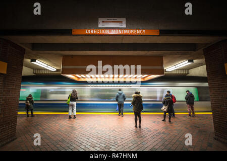 MONTREAL, CANADA - NOVEMBER 3, 2018: People waiting for a subway in Snowdon station platform, orange line, while a metro train is coming, with a speed - Stock Photo