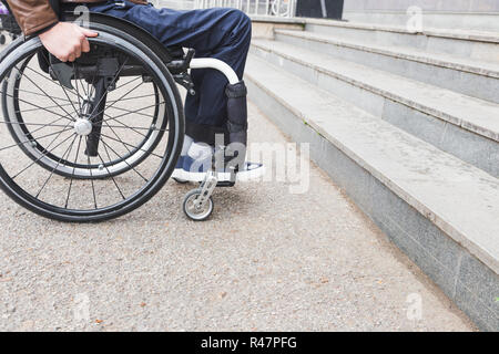 Man in wheelchair in front of stairs. - Stock Photo