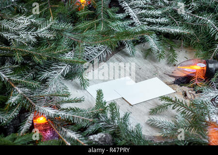 Blank business cards on christmas tree branches, new year decor and garland. - Stock Photo