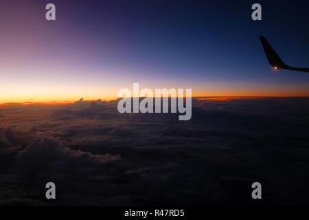 Wing of a plane in front of a beautiful sunset over clouds - Stock Photo