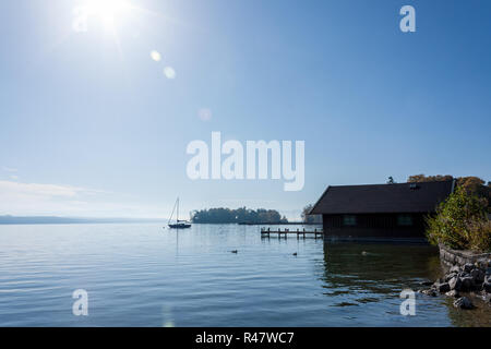 a boathouse and a boat on lake starnberg with bleuem sky and backlit - Stock Photo