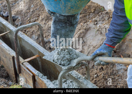 Pouring cement during upgrade to residential street - Stock Photo