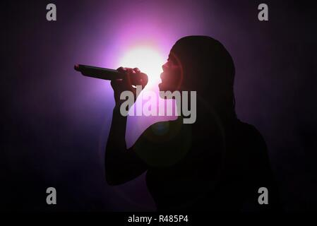 Women singing with microphone under spotlight - Stock Photo