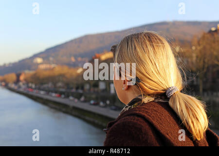 blonde tourist looks out over the river neckar in heidelberg - Stock Photo