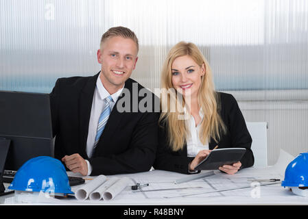 Architects Discussing Over Blueprint In Office - Stock Photo