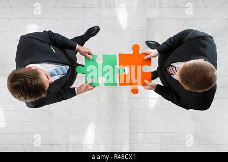 Businessmen Assembling Jigsaw Puzzle Representing Teamwork - Stock Photo