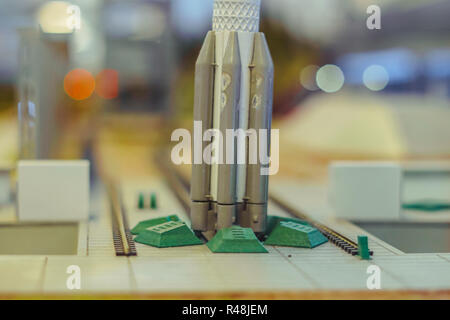 Black and white multistage space rocket model, on a miniature model of the cosmodrome - Stock Photo