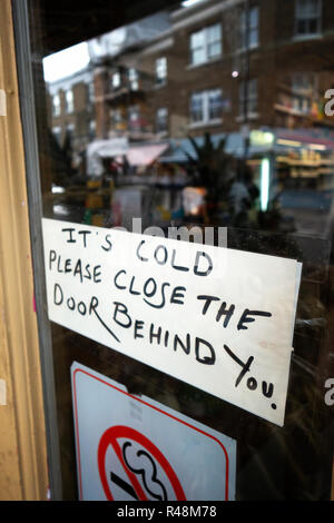Its Cold Please Close the door behind you sign on a door - Stock Photo