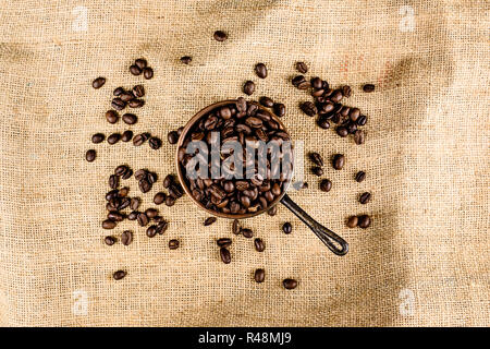 Coffee beans in a pot on brown, structured background - Stock Photo