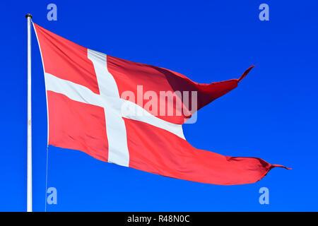 The national flag of Denmark (Dannebrog), flying high over Copenhagen, Denmark - Stock Photo