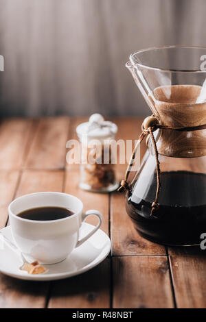 A tabletop scene with coffee, more coffee running through a coffee maker and some rock candy on a wooden table - Stock Photo