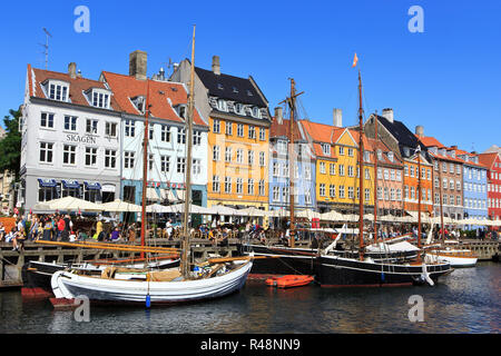 Wooden sailboats moored along Nyhavn canal with its brightly colored 17th and 18th century townhouses in Copenhagen, Denmark - Stock Photo