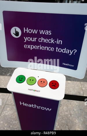 Happy or Not voting for service buttons at Check-in at Heathrow Airport International Airport in London, United Kingdom. - Stock Photo