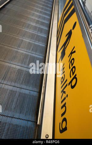 Keep Walking yellow walking man sign next to flat escalator airport walkway at Gatwick Airport in England
