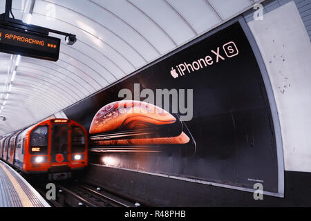 Tube train passing an ad poster for new Apple iPhone XS, advertising poster in the London Underground Track - Stock Photo
