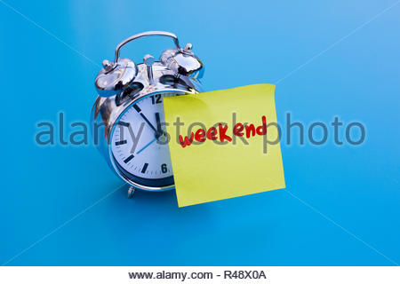 alarm clock with note 'weekend' - Stock Photo