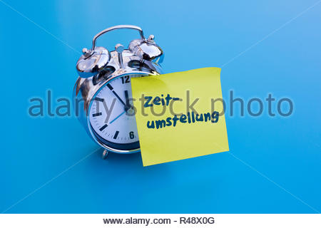 alarm clock with german word 'Zeitumstellung' (time change) - Stock Photo