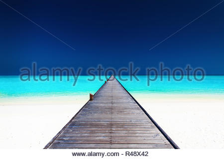 Wooden long jetty over lagoon with amazing clean water - Stock Photo