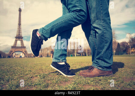 Feet of couple kissing near Eiffel tower - Stock Photo