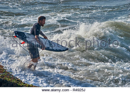 A male surfer in wetsuit, poised to launch from the rocks into the whitewater of the Pacific Ocean with board; going surfing at Yamba, NSW, Australia. - Stock Photo