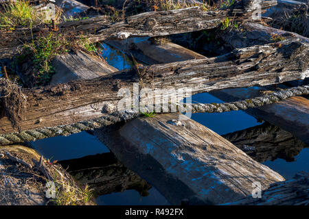 An old abandoned wooden pier from bars fastened with bolts and tied up with a rope with sprouted moss and rotten sun-bleached wood in the bay of the C - Stock Photo