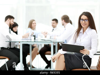 business woman signing a business document with its background blurred office - Stock Photo
