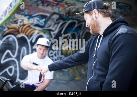 Two buddies bmxing and giving eachother a handshake in concrete ramps