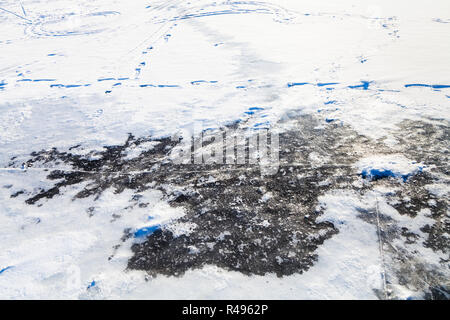 snow and ice at frozen river in winter - Stock Photo