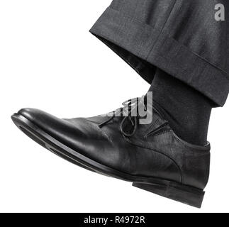 male left foot in black shoe takes a step - Stock Photo