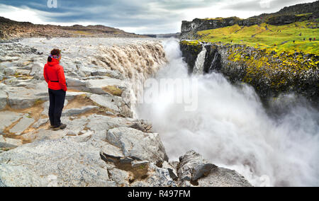 Panoramic view of woman standing near famous Dettifoss waterfall in Vatnajokull National Park, Northeast Iceland - Stock Photo