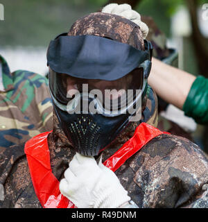 girl in face shield before playing paintball - Stock Photo