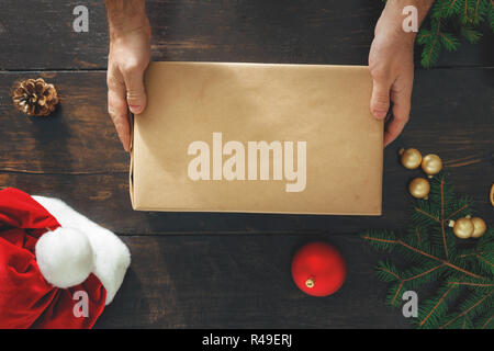 d1c130cdd9 Male hands holding big box christmas present on wooden table top view.  Rustic Christmas background