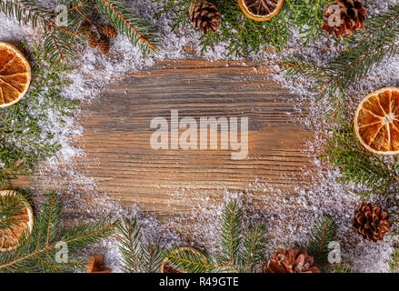Christmas frame made of fir branches, pine cones and dried orange slices on snowy wooden table - Stock Photo