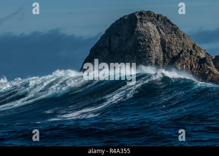 The Farallon islands jutting out of the pacific ocean as big waves roll in. - Stock Photo