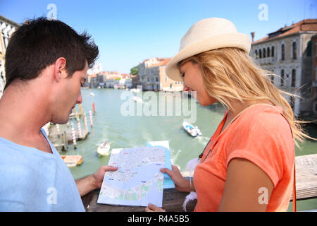 Couplelooking at map on the Academia Bridge in Venice, Italy - Stock Photo