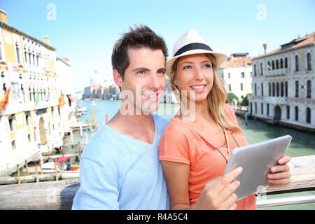 Couple using tablet on the Academia Bridge in Venice, Italy - Stock Photo