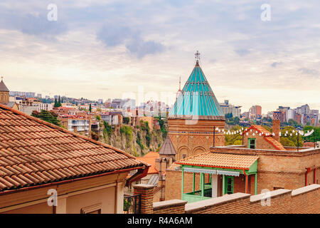 Sky over the Tbilisi Old Town neighborhood with a view on church tower and vivid red brick houses with their rooftops. Tbilisi, Georgia. - Stock Photo