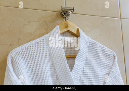 White textile bathrobe is hanging on the hook in the bathroom - Stock Photo