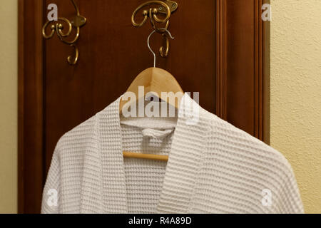 White textile robe is hanging on the hook in the bedroom - Stock Photo