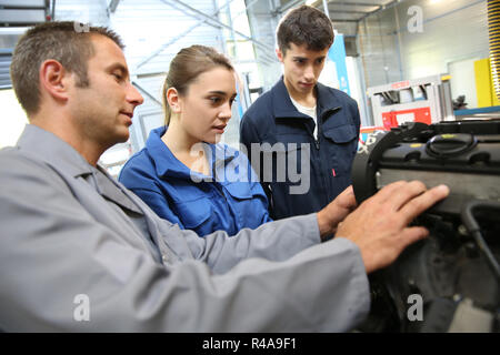 Students with instructor working on auto engine - Stock Photo