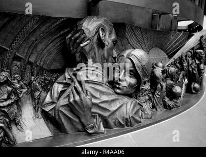 Detail of base of 'The Meeting Place' bronze statue by Paul Day in St Pancras Railway Station, Camden, London, UK. - Stock Photo